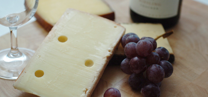Hard cheese and grapes on board
