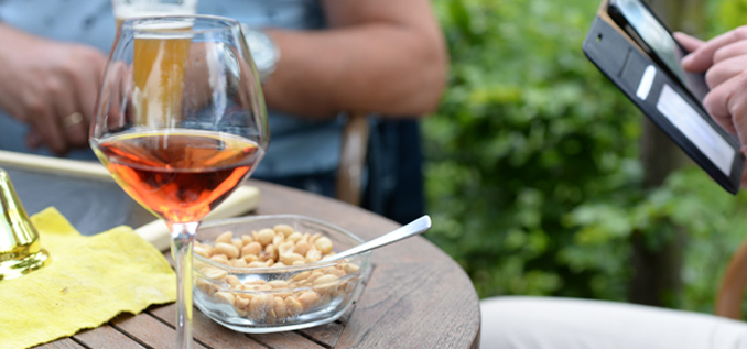 Glass on wine sits on a table next to dish of peanuts