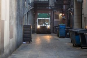 garbage truck in urban alley vibrations above restaurant wine cellar